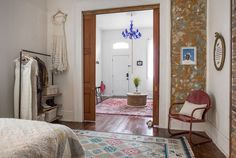 New Orleans Shotgun bedroom with exposed paint layers, pocket doors, open clothing storage rack, blue chandelier light fixture, high ceilings, period.