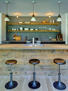 This kitchen's gorgeous custom island made from reclaimed wood brings instant character to the space. Rusted metal bar stools add industrial flair, and chic open shelving completes the eclectic look.