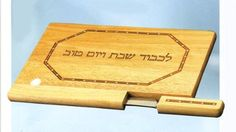 """Wood Challah Board - Design Inlay by ZionJudaica. $60.24. Elegant wood Challah board with a stainless steel matching knife - designed with contrasting wood inlay. The laser engraved letters read in Hebrew """"In honor of the holy Sabbath"""". Measures: 13 1/2"""" x 10""""."""