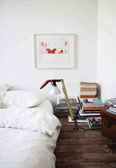 Stacks of books and an industrial lamp add a touch of quirk to a simple bedroom with the bed on the floor