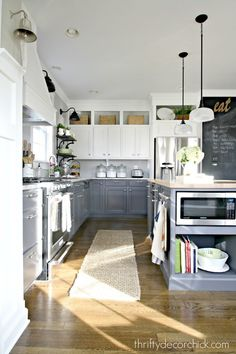 White-painted upper cabinets seem to float, while sophisticated gray-blue built-ins anchor the space.