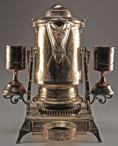 A refined circa 1879 Reed and Barton electroplated ice water server. Ornate, in the American Victorian taste, the set is comprised of four pieces, two goblets, stand and tilting porcelain lined pitcher. All of the pieces cast with rich bands of foliate designs, hand engraved icy landscapes on the goblets and pitcher. The stand, which features a tall bail handle, is designed with mounts for the goblets, as well as a removable drip tray. Just gorgeous.