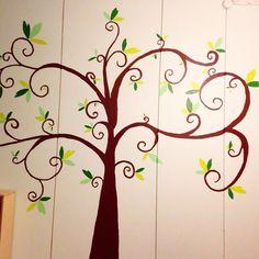 Lastenhuoneen seinä. Maalattu puu. Puunrunko on piirtoheittimen avulla piirretty seinään ja lehdet sommiteltu myöhemmin vapaalla kädellä. Puuhun tulee vielä kukkia ja pöllöjä.