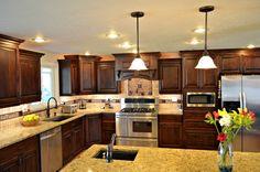 dark wood,stainless steel appliances,medium countertop, lighting