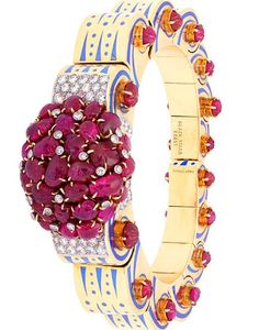 An Impressive Gold Enamel Diamond & Ruby  Bangle, Verger for Black Starr & Frost. The bangle articulated scroll design with a large cluster of carved leaf motif rubies to the centre, claw-set with circular-cut diamonds, the articulated scroll bangle with turquoise blue enamel scrolls and cabochon rubies, Circa 1940