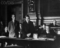 Adolf Hitler as a witness in the murder trial, 1931. One of his storm troopers was accused of murdering a political enemy. He swore he had prohibited his storm troopers to use or possess arms. At his left stands Dr. Lippert, Mayor of Berlin at that time ; at his right sits Dr Hans Frank, later Governor of Nazi-occupied Poland; in the rear, between Hitler and Lippert is the face of Rudolph Hess, former leader, third in command, of the Nazi Party. The photograph was made secretly.