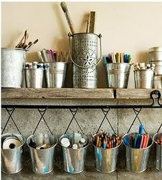 I love the look of this. Tins and buckets and an old wooden plank shelf. The buckets are hanging on wire hangers.