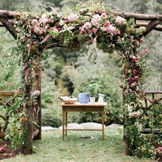 A whimsical, forest-inspired wedding arbor constructed of natural tree branches and sprinkled with wildflowers.
