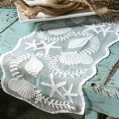 White seashell lace table runner: http://www.completely-coastal.com/2015/10/elegant-table-decorations-coastal-white.html