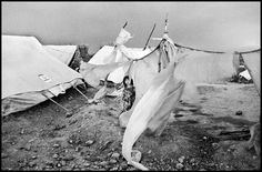 Christopher Anderson PAKISTAN. 2001. Afghan refugees in refugee camps near Peshewar. A girl stands amid tents torn by a wind storm.