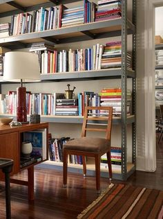 A display console and latter back chair warms up the metal bookshelf housing a collection of reference books.