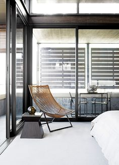 """In the master bedroom, a woven Loom chair by Matteograssi is paired with a wood-and-marble side table from Cécile & Boyd's. Sliding glass doors lead to the screened outdoor veranda with a custom bronze table and Neutra Batyline chairs from Marlanteak. """"The outside-inside flow was important to us, as the apartment is all about views and using the veranda spaces,"""" says designer Geordi De Sousa Costa. Photo by Elsa Young."""