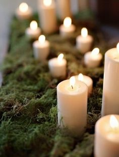 candles with moss.....like the moss table runner, would use glass hurricanes to protect the flame.