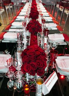 Table runners were created out of a seemingly endless array of alternating red rose petals and blooms set atop a lucite table accented with red votives. Check out this Elegant Ruby Anniversary Celebration.