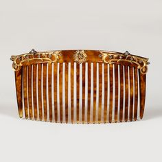 A Fabergé diamond-set tortoise shell hair comb, workmaster Erik Schramm, St Petersburg, circa 1900. Decorated with gold floral scrolls set with diamonds.