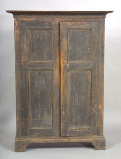 Painted Pine Cupboard, probably New York state, late 18th century, the flat deeply cove-molded cornice above two hinged doors, each with recessed molded panels, flanked by lambrequin corners, opening to four shelves, all on dovetailed bracket feet, old gray-blue paint, (imperfections), ht. 71 3/4, case wd. 45, dp. 18 1/4 in.