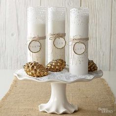 Bring the sparkling beauty of fresh snow inside with this stunning centerpiece. To get the look, top a white cake stand with coarse sugar and tall pillar candles. Finish the look with gilded gold pinecones and twine tags.