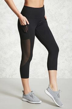 An athletic pair of knit capri leggings featuring an elasticized waistband, sheer mesh-paneled sides with slip pockets, and moisture management wicking fabric.