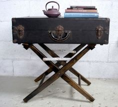 Director's chair bottom and topped it with a vintage suitcase to create a repurposed nightstand that would fit well for both him and her.