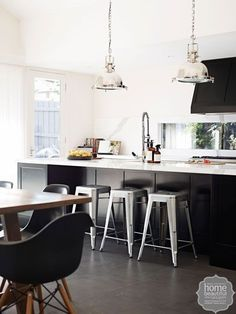 Metal stools and chrome spotlights inject touches of glamour and industrial utility to this monochrome kitchen.