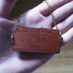Wooden Camera Necklace 📷 Perfect for any photographer! I bought this from a street vendor several years ago but only wore it once or twice. It's a wood engraved camera pendant on a gold colored chain. Super unique and pretty! NOT vintage 😊 Vintage Jewelry Necklaces