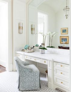 Chic dressing room features a white make up vanity adorned with brass knobs topped with white marble under a white framed mirror paired with a gray damask vanity chair atop a gray maze tiled floor.