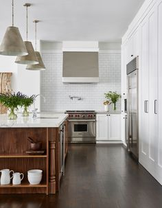 A modern and spacious kitchen featuring white cabinetry and Caesarstone countertops | archdigest.com