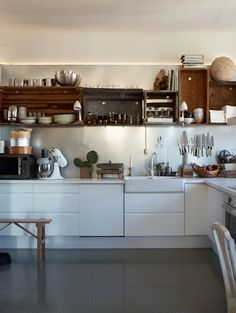 A perfect combination of modern and rustic. Old wooden crates, baskets and metal bins for upper cabinets with simple white base cabinets. I LOVE this