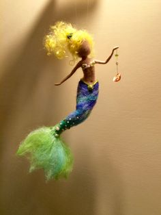 This beautiful sparkling mermaid decorate every corner of your home. It can be also nice hanger in the nursery. The mermaid is made of wool and iridescent cotton and embroidered with beads and natural pearls. Thin metal frame runs the length of the body, so it is possible to change the positions as we like. The height is about 10.