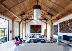When a Manhattan bachelor purchased a piece of land on Martha's Vineyard, he turned to architecture and design firm Ashe + Leandro to create the perfect getaway. The great room displays selections from his extensive art collection, including works by, from left, Howard Hodgkin, Sterling Ruby, Aaron Young, and Rashid Johnson; the bespoke ceiling lights were created in collaboration with the Urban Electric Co., the sofas and slipper chairs are by Christian Liaigre, and the striped pillows are…
