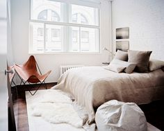 Bedroom Minimalist Photo - A leather butterfly chair and gray and beige bedding in a neutral bedroom