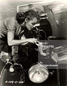 News Photo : A female mechanic works with tools under the hood...