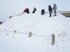 Children playing on snow pile in parking lot at Moosonee Northern Store.