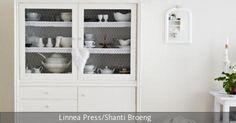 Ein weißer Küchenschrank im Vintage-Stil birgt viel Platz für Küchenutensilien. Mit Glashauben und einem dekorativen Ast wird er schön inszeniert und sorgt für eine natürliche Landhaus-Atmosphäre.