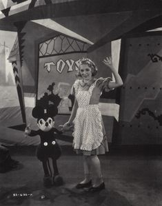 Mary Pickford on the set of Alice in Wonderland with a toy Mickey Mouse from Walt Disney, 1933.