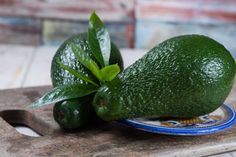 green ripe avocado with leaves on granite plank