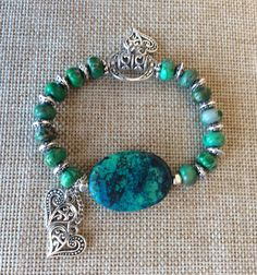 Green bead bracelet with silver heart accents