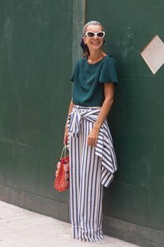 White and blue striped trousers with matching shirt tied around the waist + baggy green t-shirt + red handbag