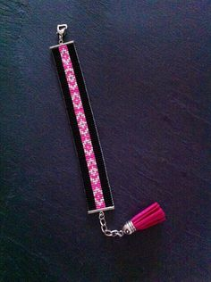 Bracelet tissé à la main. Composé de perles Miyuki rose fluo, argenté et de tubes noir.  Bracelet manchette tissé à la main par mes soins ! Fermeture réglable grâce à une chaînette d'extension terminée par un pompon en suédine, longueur maxi environ 18 cm. Fermeture soignée assurant solidité à votre bijoux. Bead loom, cuff bracelet, seed beads.