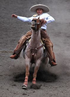 A Charro, as Mexican cowboys are known, performs a Cala de Caballo, which consists of riding a horse at full gallop and then abruptly coming to a stop, during a Charreada in Mexico City