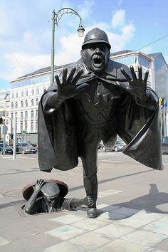 """De Vaartkapoen"" by Belgian artist Tom Frantzen is a humorous statue of a policeman being tripped by a man hiding in a sewer manhole. Created in 1985, the statue is located in Sint-Jans-Molenbeek, Belgium."