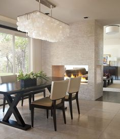 Rectangular chandelier over table dining room contemporary with trestle table dining chairs open fireplace