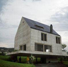 La forma exterior de la casa puede ser vista como una casa prototípica. Un techo en pendiente, una alta chimenea y grandes ventanas recuerdan a un dibujo infantil. El techo de alquitrán y  fachadas de concreto aparente fluyen casi a la perfección entre sí sin un voladizo.