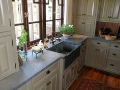Beautiful soapstone countertops. Love the way the uppers as well as the gorgeous windows meet the countertop.