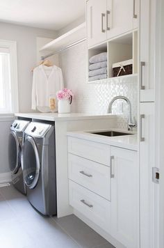 Luxury laundry room ideas, crisp neutral colors and a shimmery backsplash. Click to see the rest of our luxury laundry room inspiration in the post!