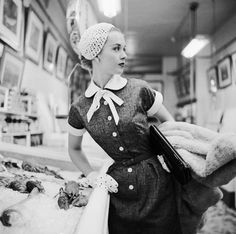 """Tippi Hedren (New Ulm, 1930) in a fish market, New York"" in 1954 by Genevieve Naylor (Springfield 1915 - New York 1989). Photograph taken before her first success with Hitchcock film (The Birds 1963). Naylor was a fashion photographer whose work appeared in Vogue, Harper's Bazaar and other magazines, although she was given a variety of photographic assignments (food, travel, and human interest). In 1979 retired from magazine work, concentrating on abstract and experimental photographs."