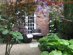 A quiet corner within a small, shaded, walled courtyard garden from a design by Sue Davis of outside-rooms.co.uk