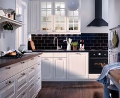 Top 15 Modern IKEA Kitchen Design Inspirations : Charming Black and White IKEA Kitchen Design with Black Ceramic Tiles Backsplash and Black Chimney also White Kitchen Cabinets White Ikea Kitchen, Ikea Kitchen Design, Ikea Kitchen Cabinets, New Kitchen, Kitchen Decor, White Cabinets, Kitchen Furniture, Kitchen Vent, Kitchen Wood