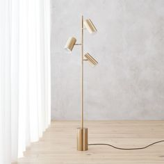 Shop trio gold floor lamp. Reading light, ambient light or spotlight—multitasking illuminator by Jannis Ellenberger does it all. Brushed in brass with perforated edge detail, trio of adjustable shades beam light all at once or one at a time via individual rotary switches.