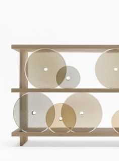 Japanese design studio Nendo designed a simple wooden storage shelf with circular-shaped glass discs that serve as the doors.
